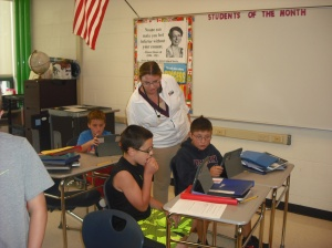 Mrs. Sturtevant looks on as a pair of students put their Geography Project together.
