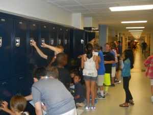 MSMS's new 6th graders scramble to test their new locker combinations.