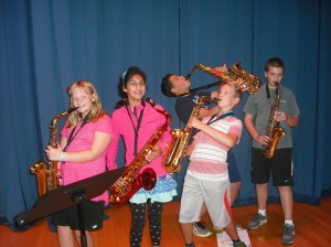An enthsiastic group of  student saxophone players warm-up before their auditions