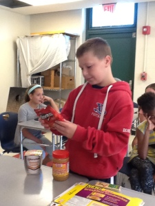 A 6th Grade boy inspecting the nutrition facts of a bag of doritos.